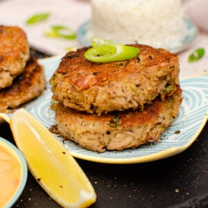 Easy Tinned Tuna Burgers on a blue,white and yellow dish served with spring onion,sliced lemon and spicy mayo sauce on the side