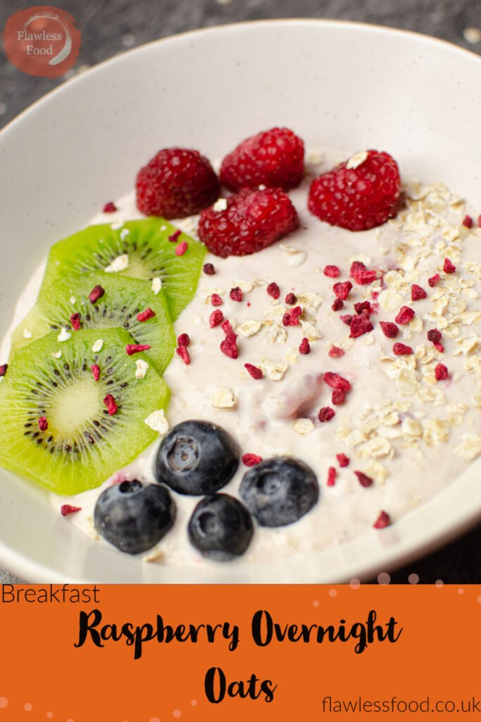 Pin image of our raspberry overnight oats served in a white bowl with fresh blueberries and raspberries on top