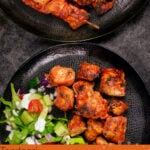 Pin image of our Tandoori Chicken Tikka Kebab served on black plates with side salad
