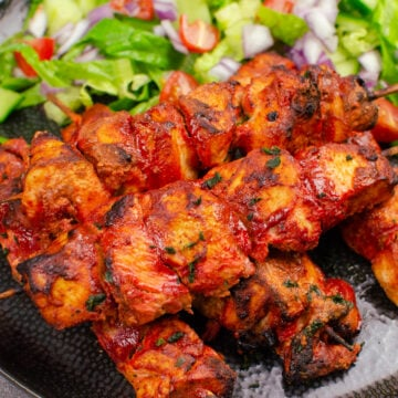 Tandoori Chicken Tikka Kebab skewers served on a black plate with salad on the side
