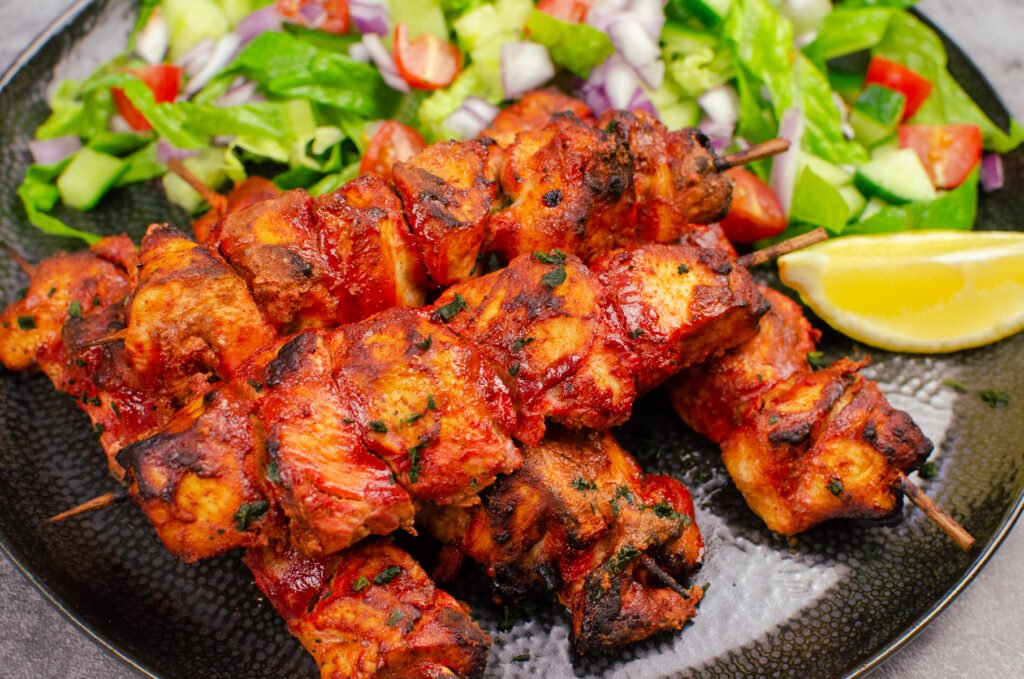 Tandoori Chicken Tikka Kebab served with a side salad and a slice of lemon on a black plate