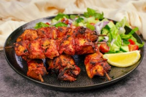 Tandoori Chicken Tikka Kebob served with a side salad and a slice of lemon on a black plate