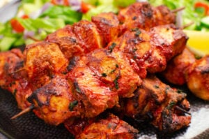 Indian chicken tikka skewers served on a black plate with a side salad and slice of lemon