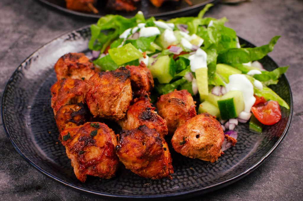 Restaurant style tandoori chicken tikka served on a black plate with a side salad drizzled with raita