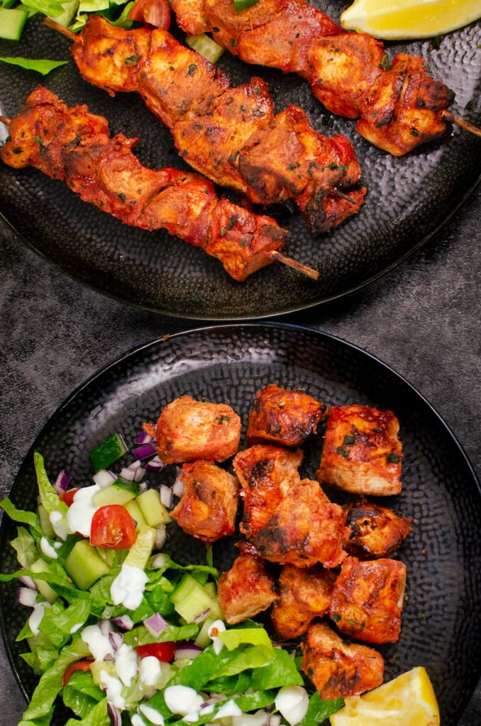 Tandoori Chicken Tikka Kebab skewers on a black plate and cubes of tikka chicken served with a side salad on another black plate