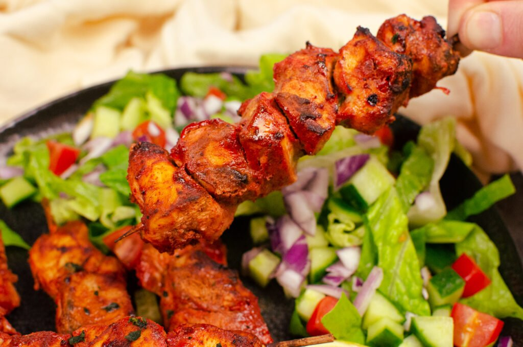 Dry chicken tikka kebabs being picked up by hand with a side salad in the background
