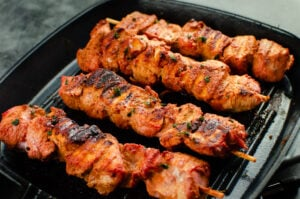 Cooked tandoori kebabs on a grey cast iron griddle