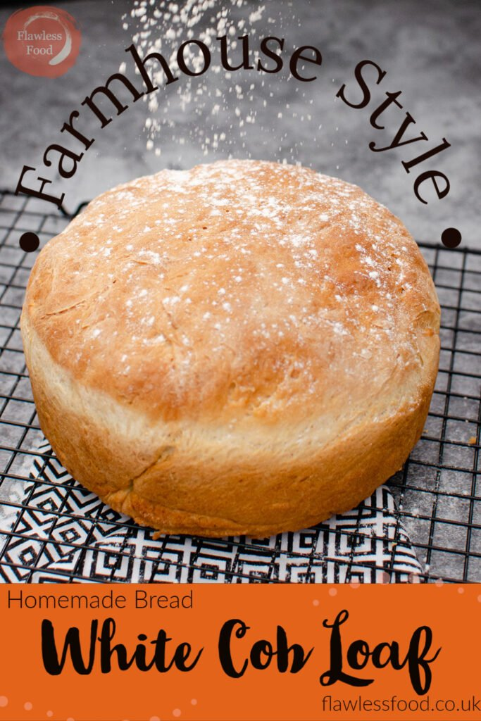 Pin image of our Homemade Bread-White Cob Loaf cooling on a wire rack with flour being sprinkled over the top