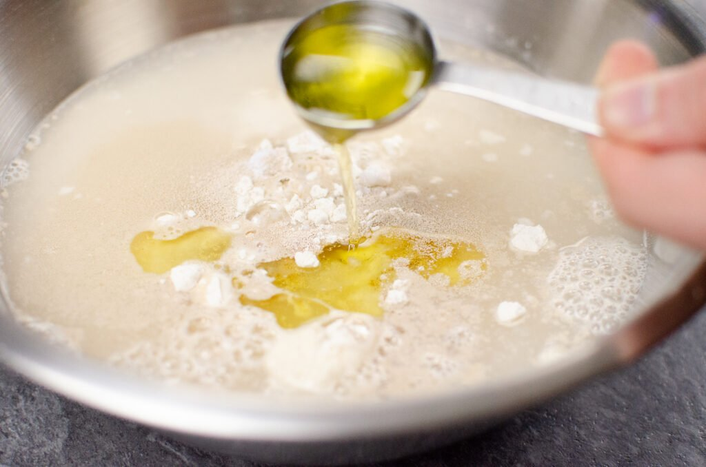 Pouring a tablespoon of olive oil into a silver mixing bowl with flour, yeast and water