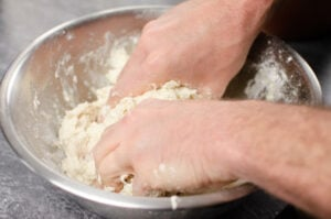 Kneading bread dough in a silver bowl by hands in a silver mixing bowl