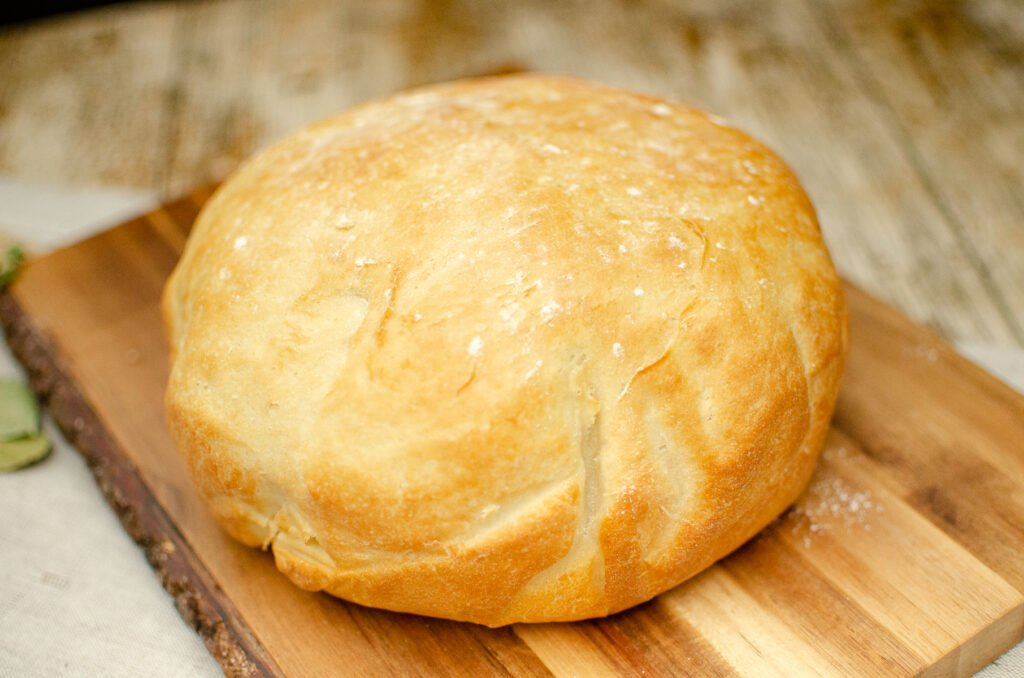 Homemade Bread-White Cob Loaf on a brown wooden chopping board