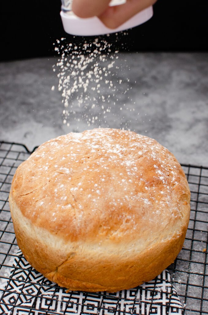 Sprinkling flour over the top of our bread with a flour shaker