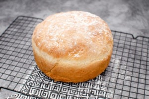 Round crusty loaf of bread on a an airing rack with sprinkled flour on top