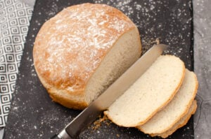 Homemade bread on black slate being cut into slices with a large silver knife