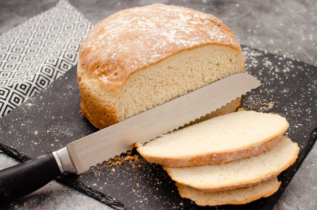 White cob loaf on black slate being cut into slices with a large silver knife
