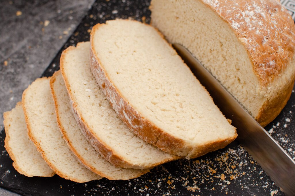 A white loaf of homemade cooked bread on black slate being cut into slices with a large silver knife