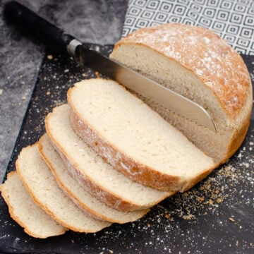 British white cob loaf being sliced with a silver knife on a black piece of slate