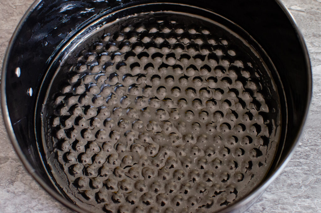 A greased black cake tin