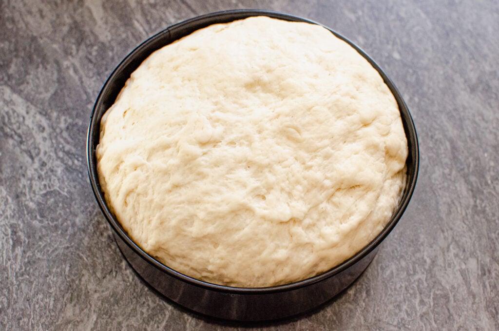 white bread dough in a black cake tin