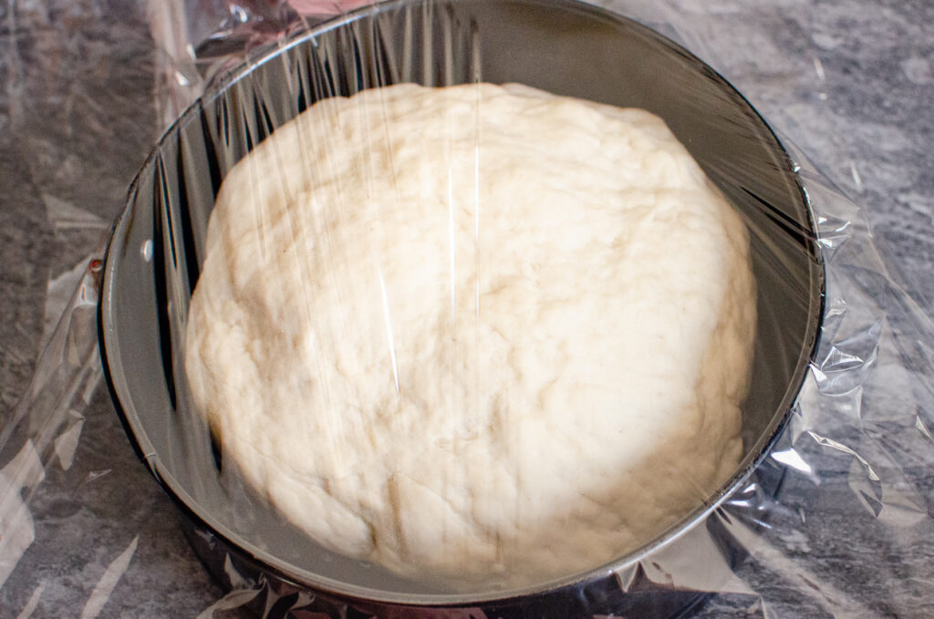Covering the bread dough with cling film