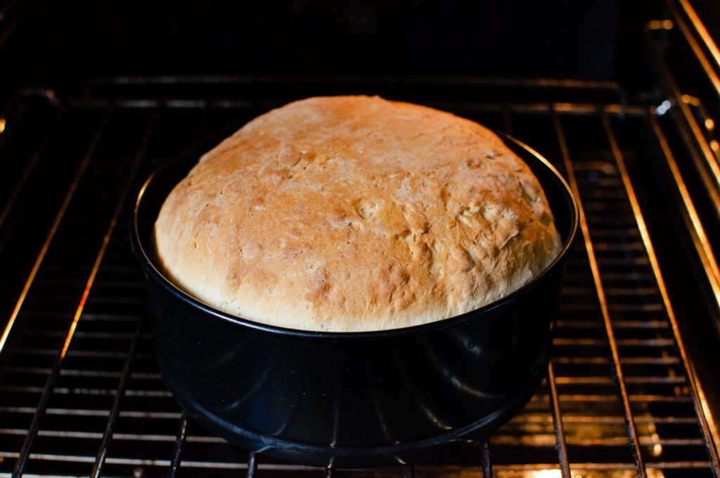 Homemade bread - white cob loaf cooked in a black cake tin in the oven