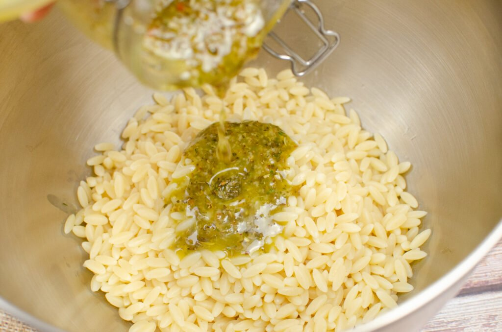 Pouring Mediterranean dressing onto cooked orzo in a silver large mixing pot