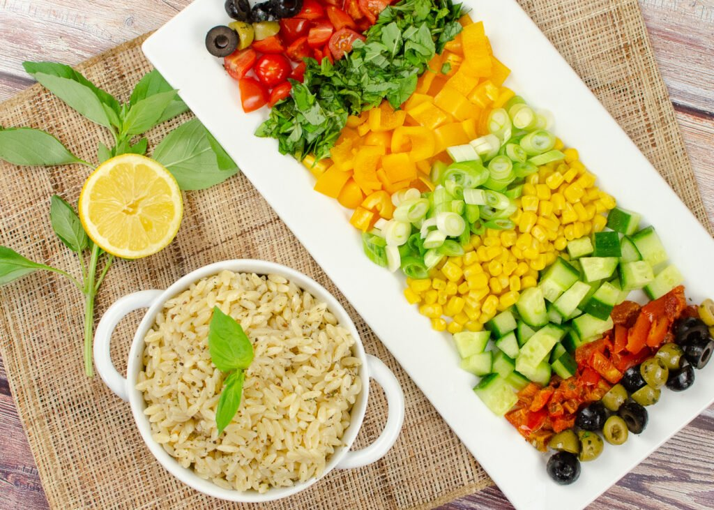 Summer salad consisting off Chopped green, black olives, tomatoes,basil,yellow pepper, spring sun dried tomatoes and green and black olives served in sections on a long square plate with orzo in a white bowl, mozzarella balls, lemon and fresh basil on the sides