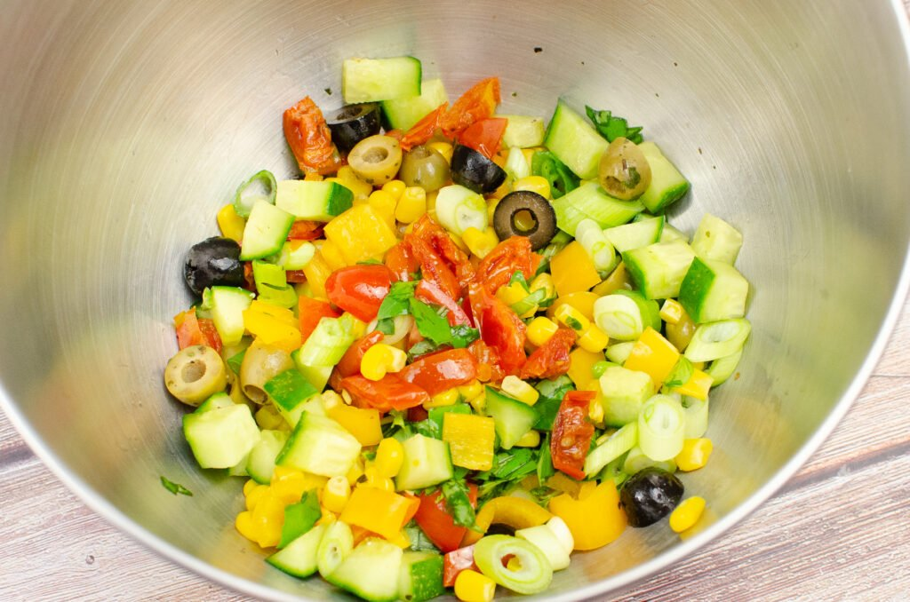 Chopped green, black olives, tomatoes,basil,yellow pepper, spring sun dried tomatoes in a silver bowl