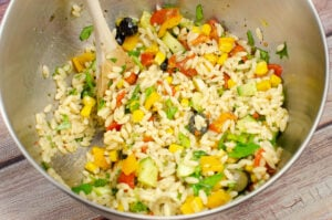 Chopped green, black olives, tomatoes,basil,yellow pepper, spring sun dried tomatoes and the cooked orzo being mixed together with a wooden spoon in a silver bowl