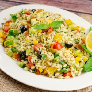 Fresh Orzo Pasta Salad served on a large white plate with fresh basil leaves and a lemon slice on the side