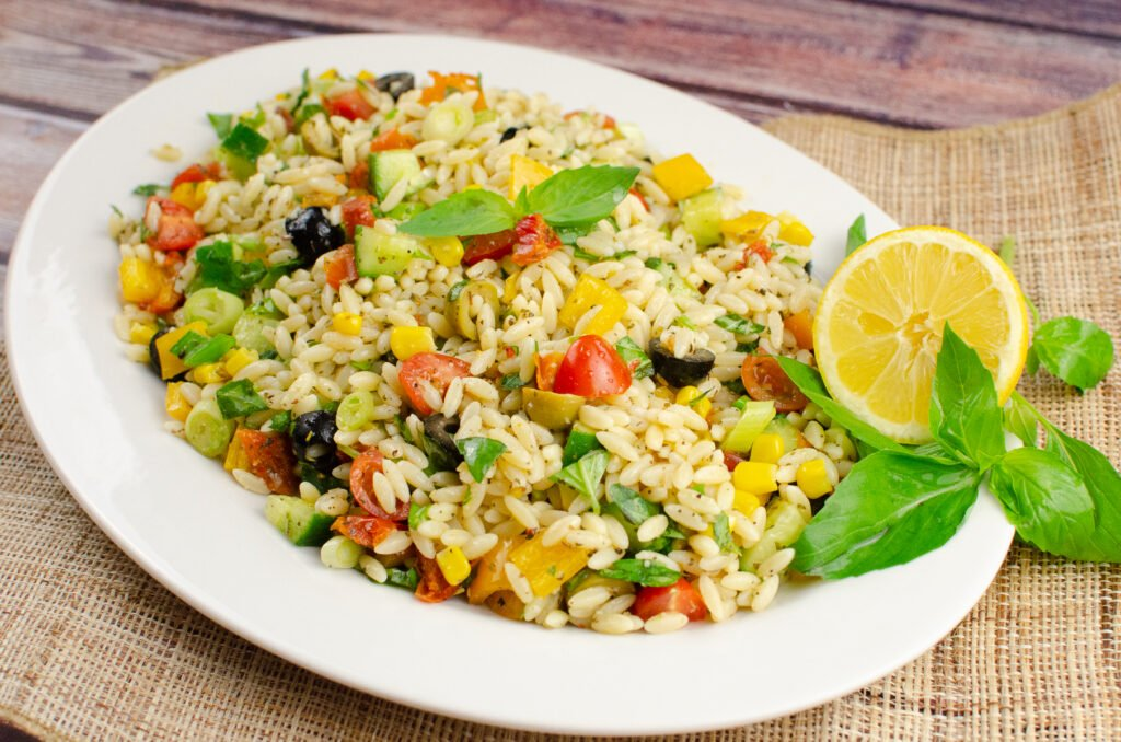 Fresh Orzo Pasta Salad lunch served on a large white plate with fresh basil leaves and a lemon slice on the side