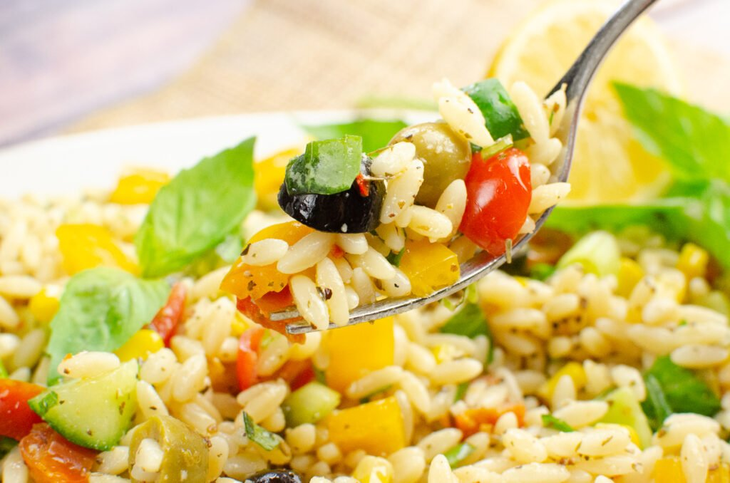 Summer Orzo Pasta Salad being picked up on a silver fork