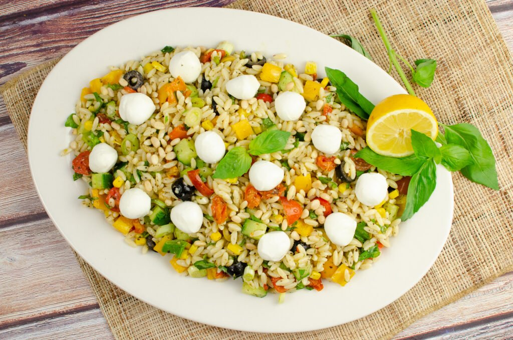 Healthy Orzo Pasta Salad served on a large white plate with mozzarella balls on top with fresh basil leaves and a lemon wedge on the side