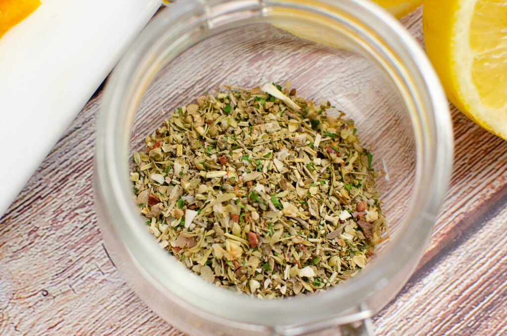 Italian mixed herbs in a clear glass pot with a lemon slice on the side