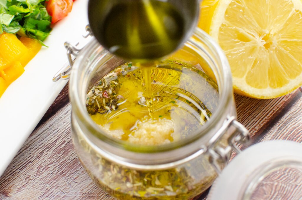 Olive oil being poured into a glass pot with Italian herb seasoning and garlic