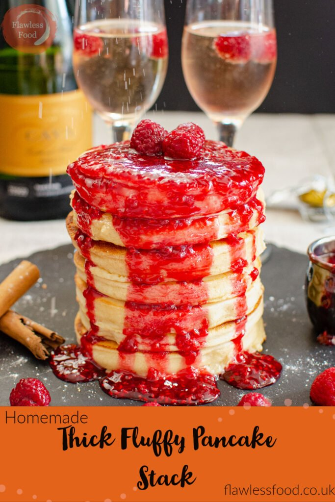 Pin image of Thick Fluffy Pancake Stack covered in raspberry sauce served on a black slate plate with glasses of champagne in the background with cinnamon sticks and a pot of raspberry sauce on the sides