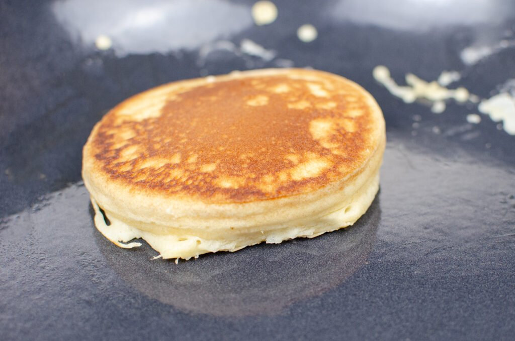 Fluffy pancake cooking on a cast iron pan