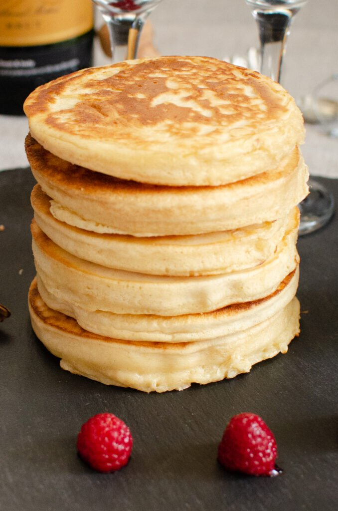 Thick Fluffy Pancakes Stack served black slate with two fresh raspberries in front and two champagne glasses in the background