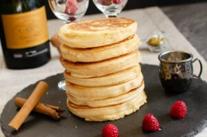 Thick Fluffy Pancakes served on a black piece of slate with fresh raspberries, cinnamon sticks,bottle of cava, two champagne glasses with raspberries inside and a small jug of raspberry sauce around the stack