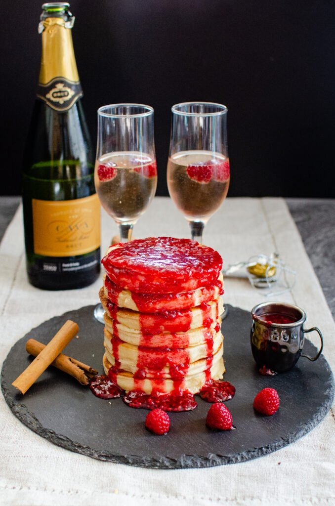 Sweet Pancakes covered in raspberry sauce served on a black piece of slate with fresh raspberries, cinnamon sticks, two champagne glasses and a small jug of raspberry sauce around the stack