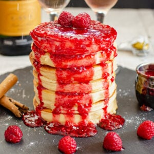 Thick Fluffy Pancakes covered in fresh raspberries and raspberry sauce and sprinkled icing sugar on top served on a black piece of slate with fresh raspberries, cinnamon sticks, two champagne glasses filled with champagne and fresh raspberries inside and a small jug of raspberry sauce around the stack