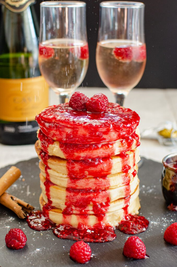 Fancy Fluffy Pancakes covered in raspberry sauce served on a black piece of slate with fresh raspberries, cinnamon sticks, two champagne glasses filled with champagne and fresh raspberries inside and a small jug of raspberry sauce around the stack