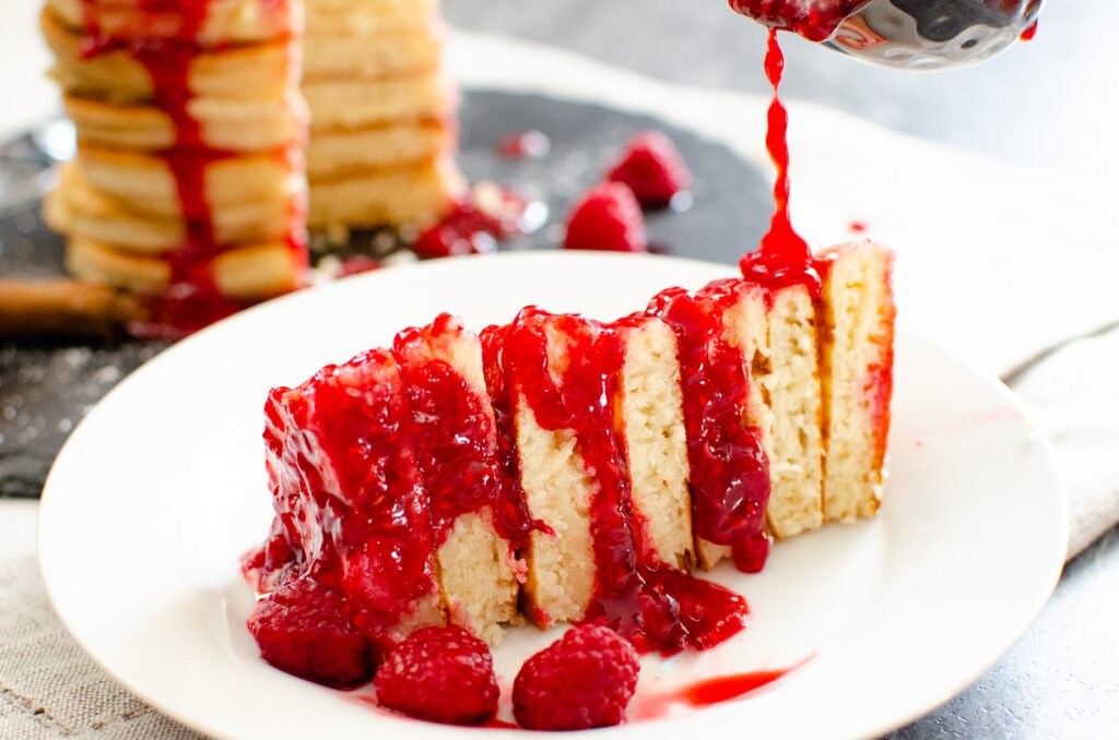 A quarter of stack of pancakes served in a white bowl with fresh raspberry sauce being poured over the top with fresh raspberries on the side