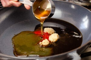 Garlic, chilli, soy sauce and ginger in a cast iron pan with honey being poured over the top from ¼ measuring cup