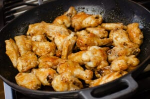 Chicken wings into a cast iron pan coated in with the honey and garlic glaze
