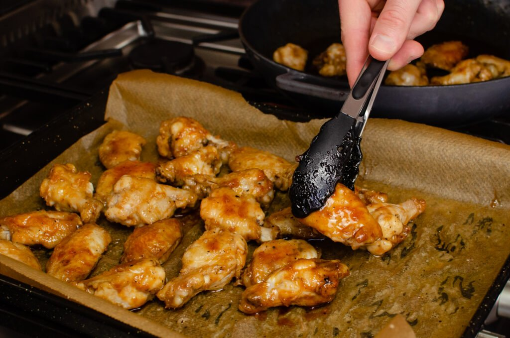 Placing the coated chicken wings by black and silver tongs onto a lined baking tray lined with parchment paper