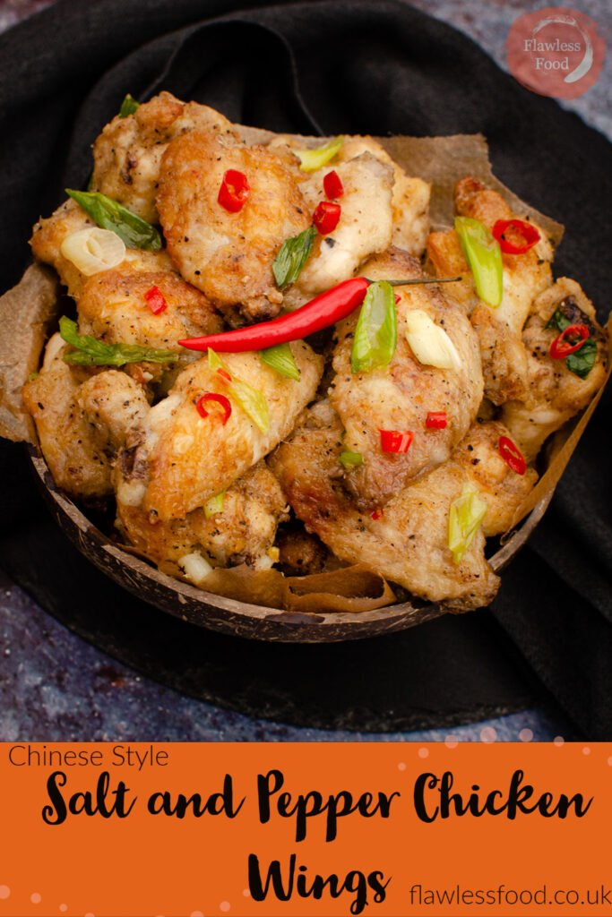 Salt and pepper chicken wings served in a coconut bowl garnished with chopped spring onion and chopped red chillies