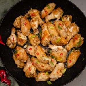 salt and pepper chicken wings in a cast iron pan garnished with chopped spring onion and red chilli