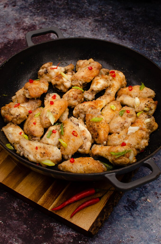 salt and pepper chicken wingettes and drumettes in a cast iron pan garnished with spring onion and red chillies