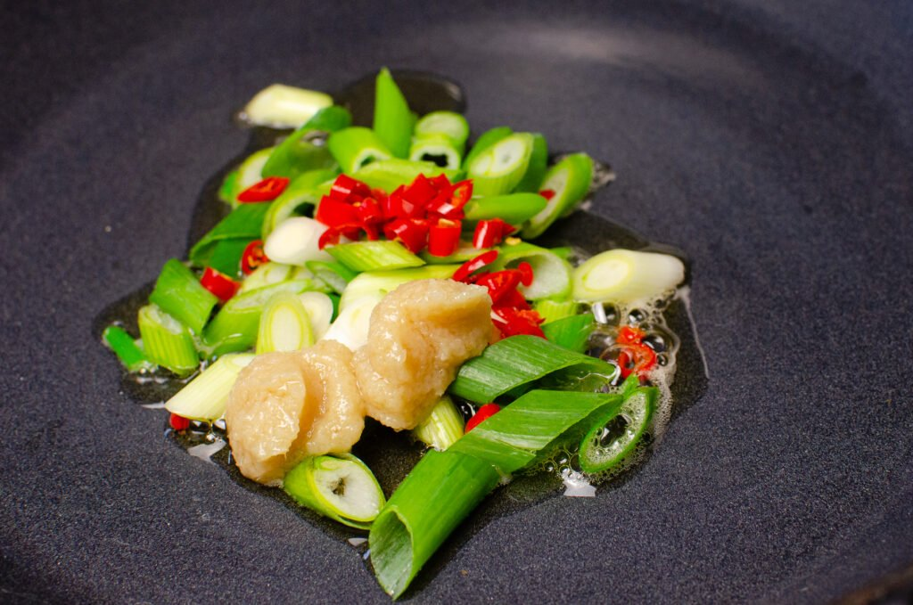 Sesame oil,chopped spring onion, chopped red chilli and garlic cooking on a cast iron pan